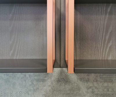 Basi con anta a telaio, maniglia integrata in grigio abbinata a pensili monolaccati lisci. Mensole decorative con dettagli metallo ramato.