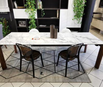 Tavolo 90x130, allungabile a 260cm. Gambe sempre perimetrali in legno finitura noce, piano in gres porcellanato finitura marmo bianco lucido, con vena continua nelle allunghe.